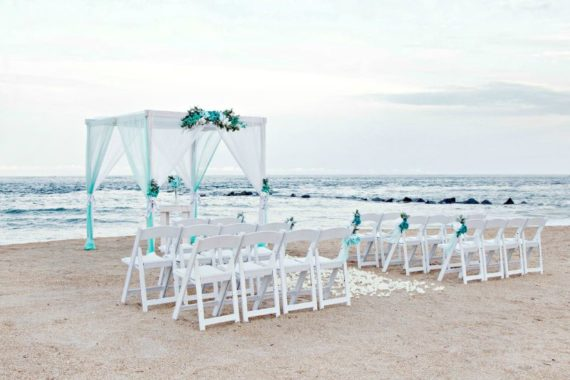 White 4-post arbor and chairs on the beach